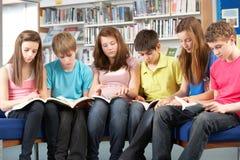 Estudiantes adolescentes en libros de lectura de la biblioteca Imagen de archivo libre de regalías