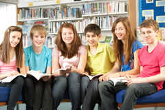 Estudiantes adolescentes en libros de lectura de la biblioteca foto de archivo