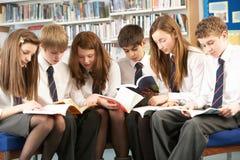 Estudiantes adolescentes en libros de lectura de la biblioteca Fotografía de archivo libre de regalías