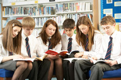 Estudiantes adolescentes en libros de lectura de la biblioteca Fotos de archivo libres de regalías