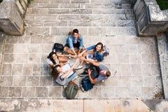Estudiantes adolescentes en los pasos de piedra delante de la universidad Imagen de archivo