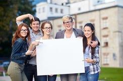Estudiantes adolescentes felices que llevan a cabo al tablero en blanco blanco Foto de archivo