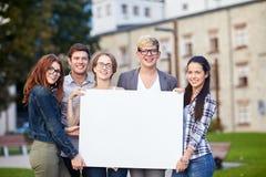 Estudiantes adolescentes felices que llevan a cabo al tablero en blanco blanco Fotos de archivo libres de regalías