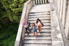 Estudiantes adolescentes que caminan en los pasos de piedra delante de la universidad Fotos de archivo libres de regalías