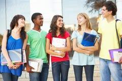 Estudiantes adolescentes que colocan el edificio exterior de la universidad Fotos de archivo