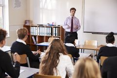 Estudiantes adolescentes que escuchan el profesor de sexo masculino In Classroom foto de archivo libre de regalías