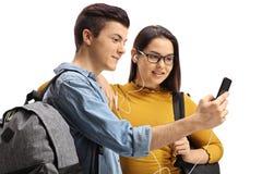 Estudiantes adolescentes que escuchan la música en un teléfono Fotos de archivo