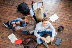 Estudiantes adolescentes que estudian en el piso Fotografía de archivo libre de regalías