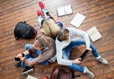 Estudiantes adolescentes que estudian en el piso Foto de archivo