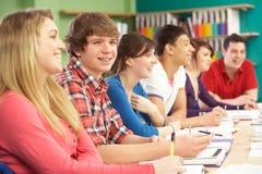 Estudiantes adolescentes que estudian en sala de clase foto de archivo