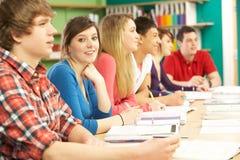 Estudiantes adolescentes que estudian en sala de clase Imagen de archivo libre de regalías