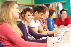 Estudiantes adolescentes que estudian en sala de clase Imagenes de archivo
