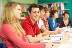 Estudiantes adolescentes que estudian en sala de clase Foto de archivo libre de regalías