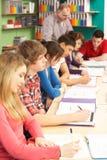 Estudiantes adolescentes que estudian en sala de clase con el profesor particular Imagen de archivo