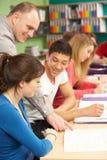 Estudiantes adolescentes que estudian en sala de clase con el profesor particular Fotos de archivo libres de regalías