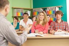 Estudiantes adolescentes que estudian en sala de clase con el profesor particular Imagenes de archivo