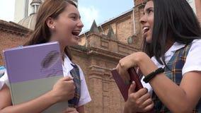 Estudiantes adolescentes que hablan sosteniendo los libros de texto Imagen de archivo