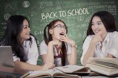 Estudiantes adolescentes que hablan y que ríen en clase Imagen de archivo libre de regalías