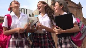 Estudiantes adolescentes que hablan y que sostienen los libros Foto de archivo