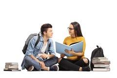 Estudiantes adolescentes que leen un libro en el piso Imagenes de archivo