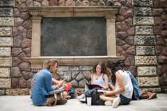 Estudiantes adolescentes que se sientan en la tierra delante de la universidad Fotos de archivo