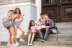 Estudiantes adolescentes que se sientan en los pasos de piedra delante de la universidad Fotos de archivo