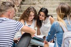 Estudiantes adolescentes que se sientan en los pasos de piedra delante de la universidad Foto de archivo