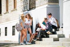 Estudiantes adolescentes que se sientan en los pasos de piedra delante de la universidad Imagen de archivo libre de regalías