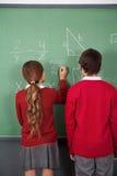 Estudiantes adolescentes que solucionan matemáticas a bordo Fotos de archivo libres de regalías