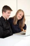 Estudiantes adolescentes que trabajan en el ordenador Imágenes de archivo libres de regalías