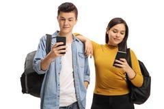 Estudiantes adolescentes que usan los teléfonos Fotos de archivo