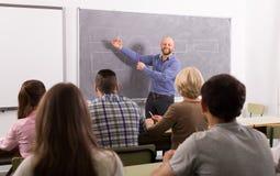 Estudiantes adultos con el profesor en sala de clase Foto de archivo libre de regalías