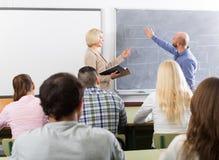 Estudiantes adultos con el profesor en sala de clase Imágenes de archivo libres de regalías