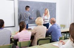 Estudiantes adultos con el profesor en sala de clase Fotos de archivo libres de regalías