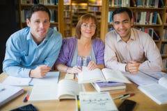 Estudiantes adultos que estudian junto en la biblioteca Imagen de archivo