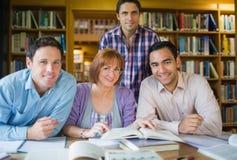 Estudiantes adultos que estudian junto en la biblioteca Imagenes de archivo