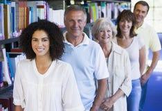 Estudiantes adultos que se colocan en una biblioteca Imagen de archivo