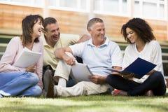 Estudiantes adultos que se sientan en un césped del campus imagenes de archivo