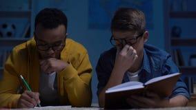 Estudiantes afroamericanos y caucásicos que intentan solucionar la asignación difícil, prueba almacen de metraje de vídeo