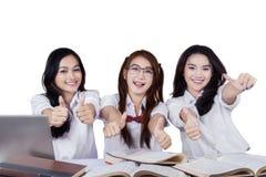 Estudiantes alegres con los pulgares para arriba Imagen de archivo