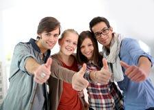 Estudiantes alegres con los pulgares para arriba Imagenes de archivo