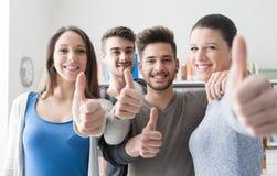 Estudiantes alegres con los pulgares para arriba Fotografía de archivo libre de regalías