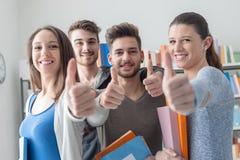 Estudiantes alegres con los pulgares para arriba Foto de archivo