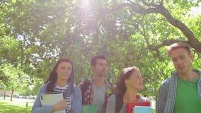 Estudiantes alegres que caminan afuera almacen de video
