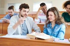 Estudiantes alegres que discuten el libro de texto en la rotura antes de seminario Imagenes de archivo