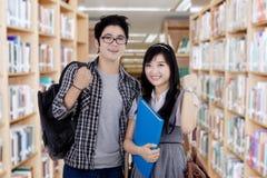 Estudiantes alegres que expresan éxito en biblioteca Foto de archivo