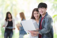 Estudiantes asiáticos en cuaderno del ordenador del uso de la universidad fotos de archivo