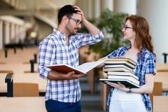 Estudiantes atractivos jovenes que pasan tiempo en biblioteca Fotografía de archivo