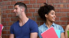 Estudiantes bonitos que cuelgan hacia fuera en campus metrajes