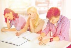 Estudiantes cansados con los cuadernos en la escuela Imagen de archivo